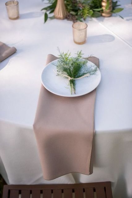 simple place setting with a grey napkin and fresh greenery
