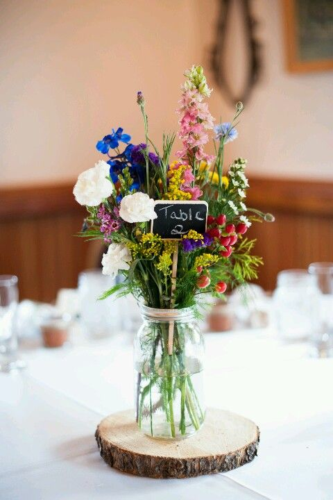 bold wildflower centerpiece with a chalkboard table number on a wood slice
