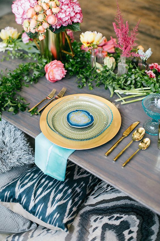 colorful boho chic table setting with florals and bold plates