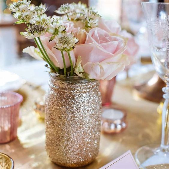 glittery gold mason jar with flowers as a centerpiece