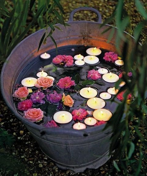 a galvanized bathtub with floating candles and flowers