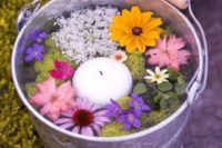 21 a galvanized bucket with flowers and a floating candle