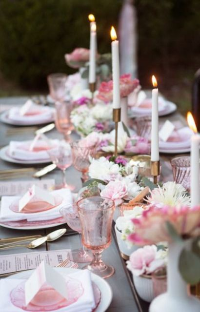 grey table with pink glasses, plates and florals look cool and bold
