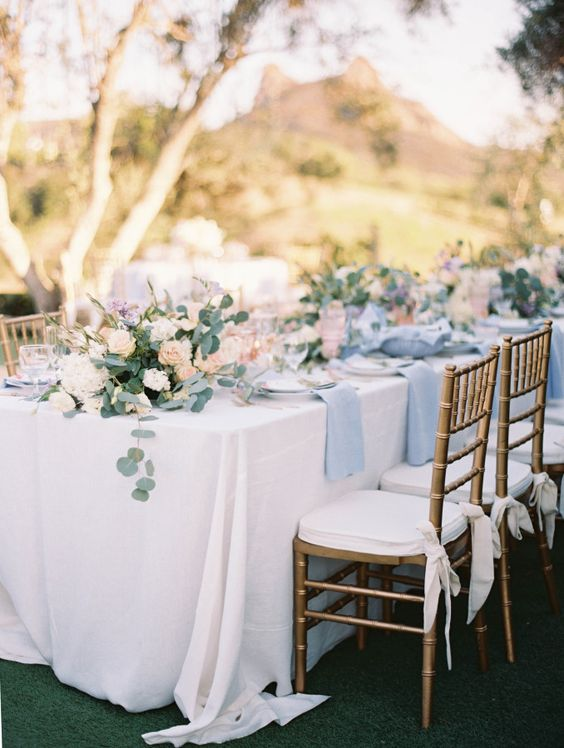 outdoor wedding reception in white and serenity blue with greenry