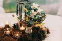 23 moss, greenery and flowwers, candles for a cute centerpiece
