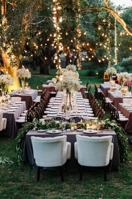 outdoor spring wedidng reception with fresh greenery and hanging lights