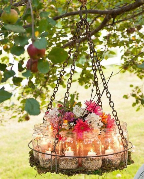 chandelier with jars with candles and fresh flowers