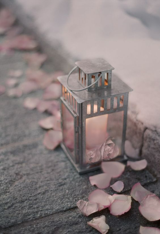galvanized lantern with a candle and pink petals