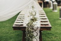 24 rustic table with lace table runner, fresh greenery over it
