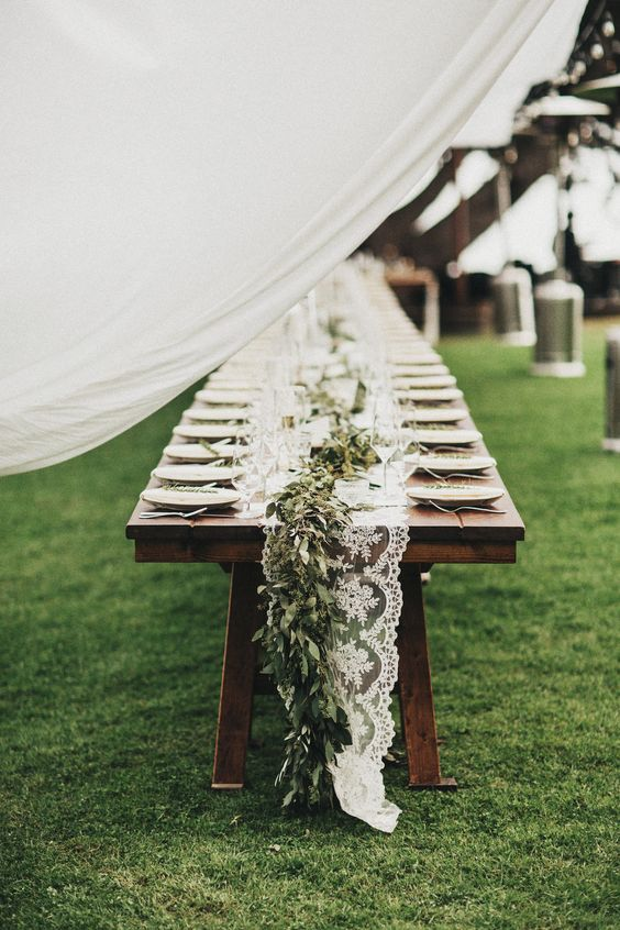 rustic table with lace table runner, fresh greenery over it