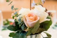 25 galvanized bucket with blush roses and leaves and a wood slice table number