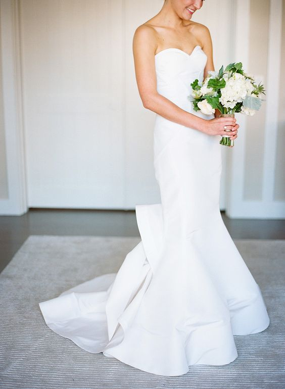 sleek wedding dress with a mermaid silhouette and a bow on the back