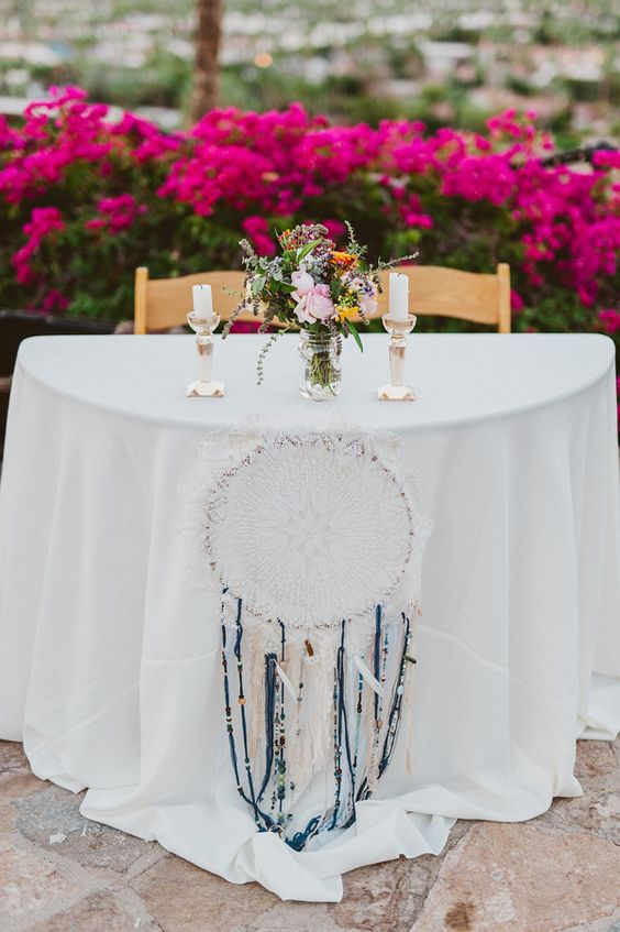 sweetheart table with a dream catcher, flowers and candles
