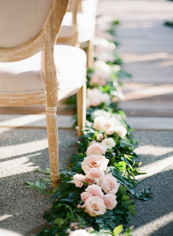 blush roses and greenery garland that goes along the aisle