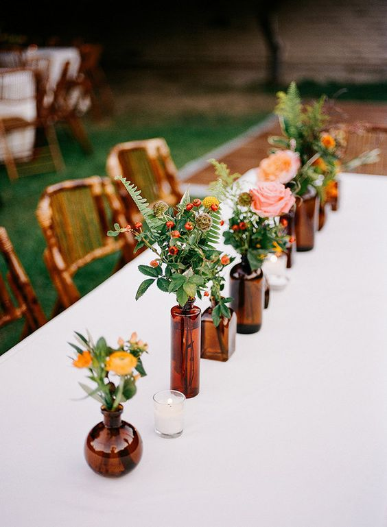 simple flower table runner in glass bottles and vases of the same color