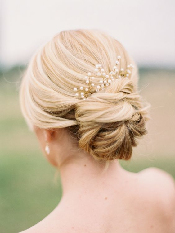 simple low bun updo with a pearl hairpiece
