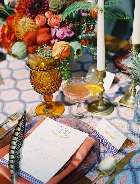 super bold boho chic table setting with candles and feathers