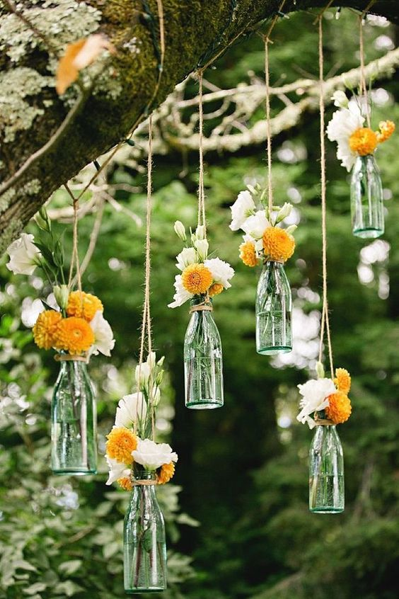 hanging bottles with white and yellow flowers over the reception