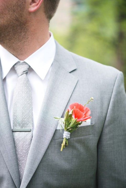 light grey suit and tie, a red flower boutonniere