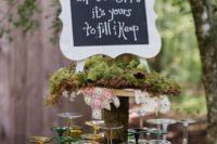30 colorful glasses on a stand with moss and a chalkboard sign