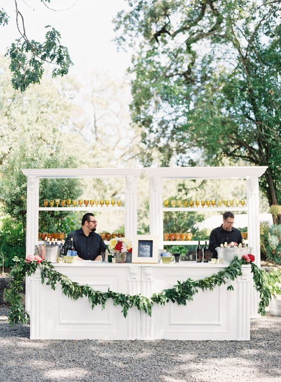 white drink bar with a greenery garland