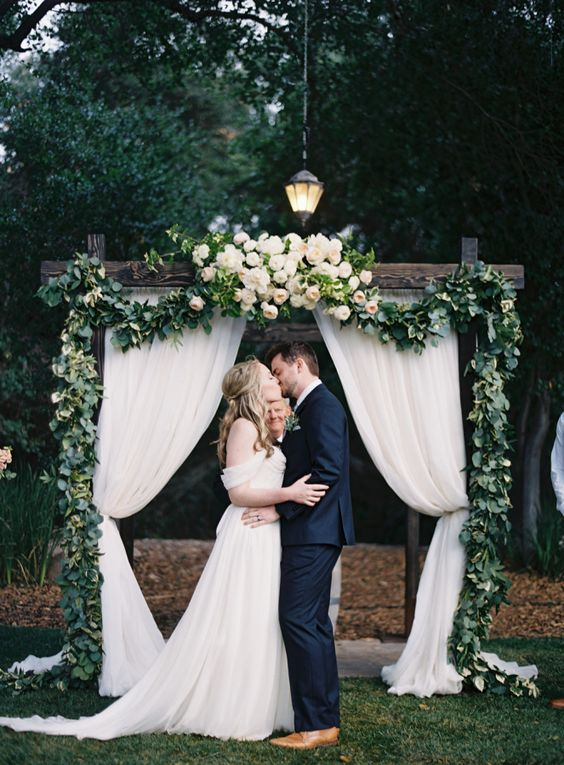 elegant stained wooden arch with blush blooms and curtains