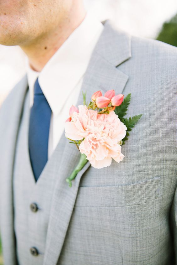 light grey suit with a vest, a navy tie and a peach-colored flower boutonniere
