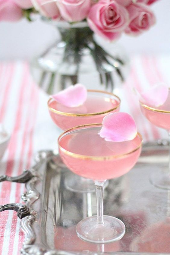 pink signature cocktails with petals in gold rim glasses