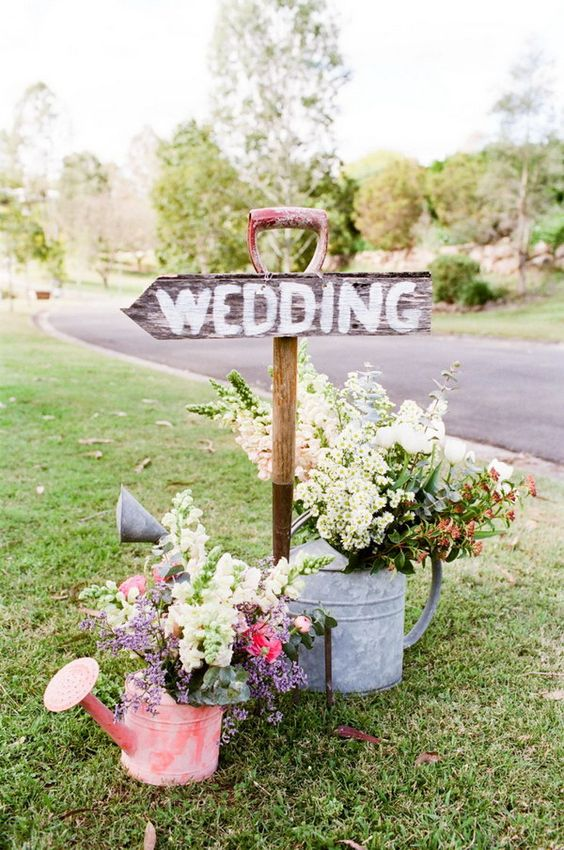 wedding sign with watering cans instead of vases