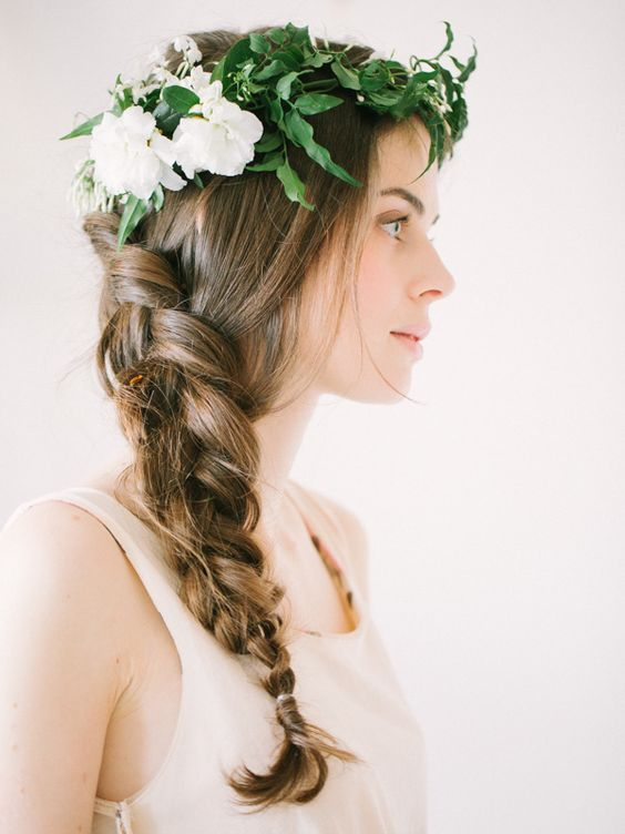 curled side swept hairstyle with a floral crown