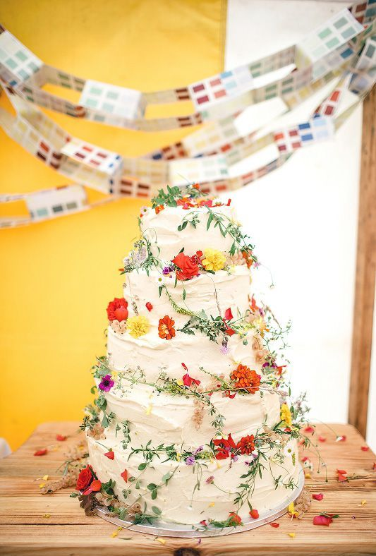 multi-tiered wedding cake with red and yellow wildflowers