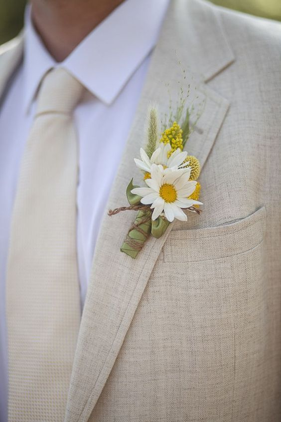 tan suit and tie, a yellow and white flower boutonniere