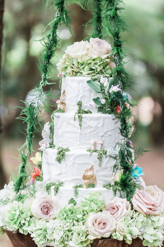 cream wedding cake with lush floral and greenery decor