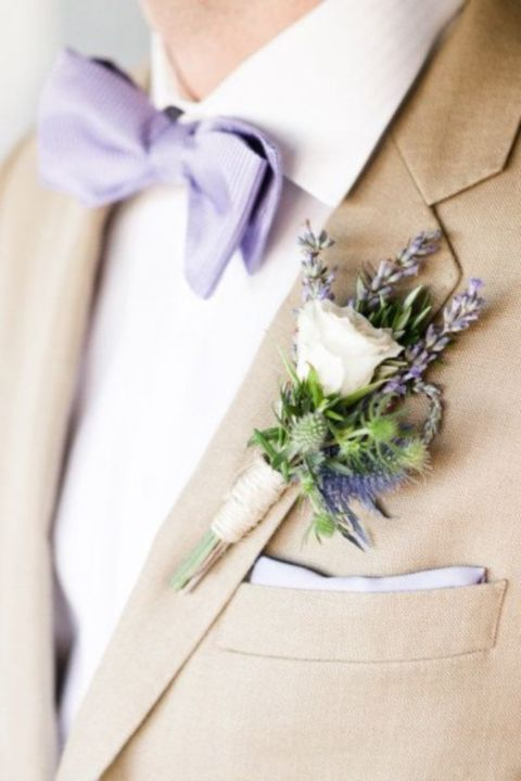 tan suit, a white shirt, a lavender bow tie