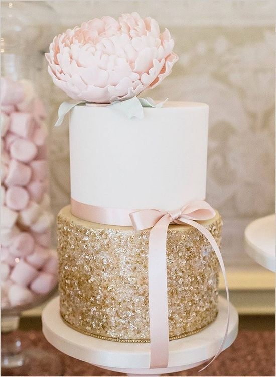 white and glitter gold wedding cake with a blush bloom and ribbon