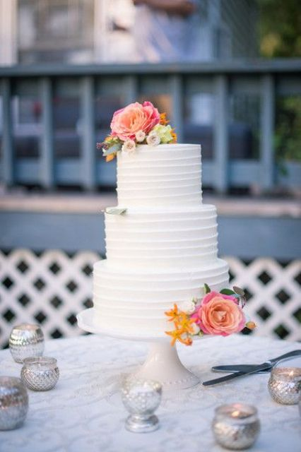 white wedding cake with bright fresh flowers