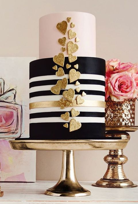 black and white striped wedding cake decorated with glitter gold hearts