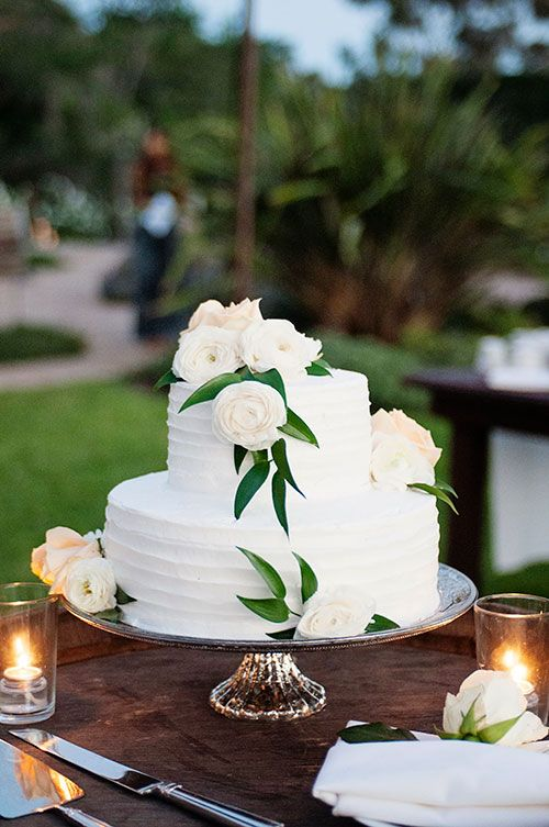 white wedding cake with white flowers and greenery