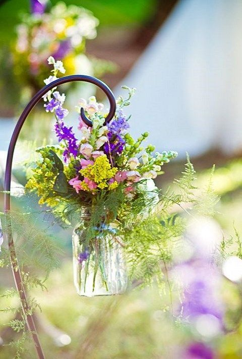 colorful wildflowers in a jar for decorating the aisle