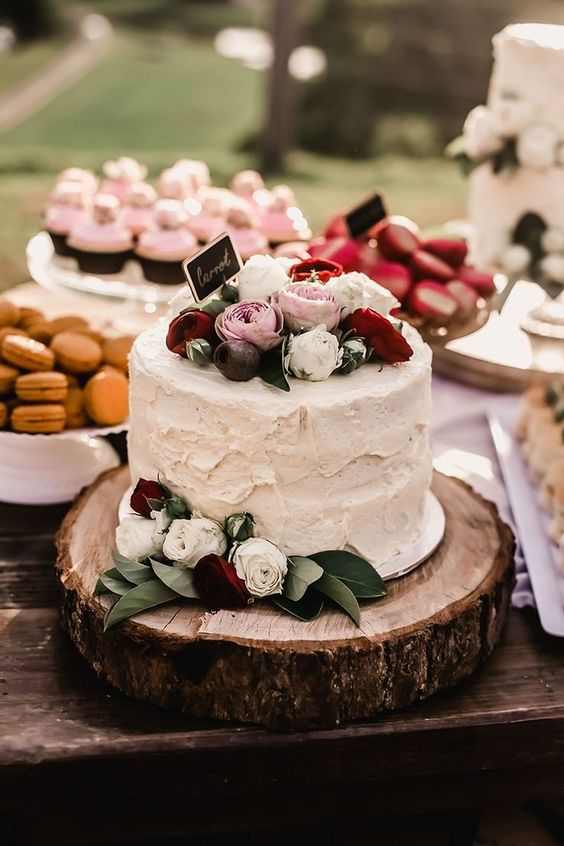 rustic buttercream wedding cake with pink, red and white roses on a wood round