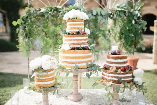 multiple naked wedding cakes with botanical decorations