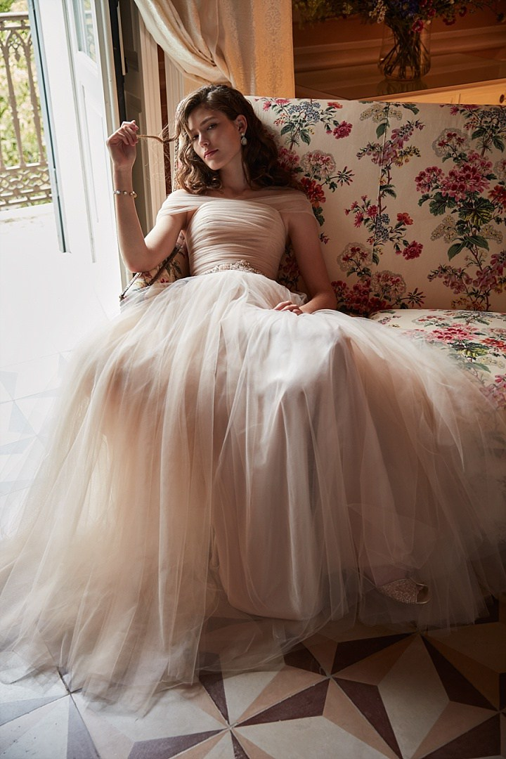 Ramona gown in delicate champagne tulle, off the shoulder details, a ruched bodice, and voluminous skirt make this gown a romantic's dream