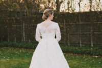 02 Lace wedding dress with an illusion back with buttons and an elegant low bun is what the bride has chosen