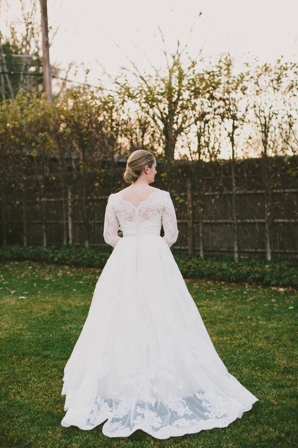 Lace wedding dress with an illusion back with buttons and an elegant low bun is what the bride has chosen