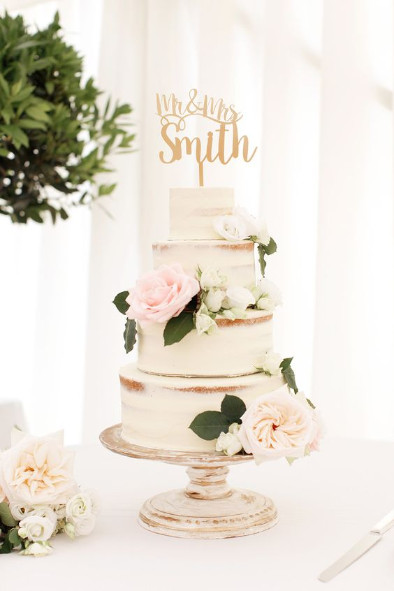 semi naked three tiered wedding cake with fresh flowers and a calligraphy topper