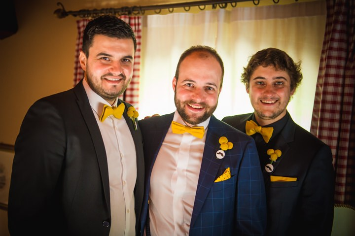 The groom was wearing a blue suit, a white shirt and a yellow billy ball boutonniere