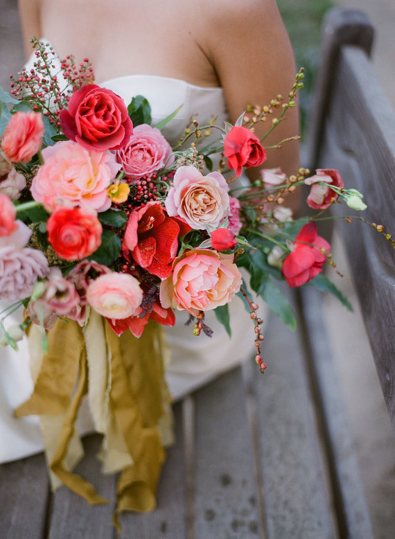 The wedding bouquet was filled with pink, red and other bold colors, with berries and yellow ribbon