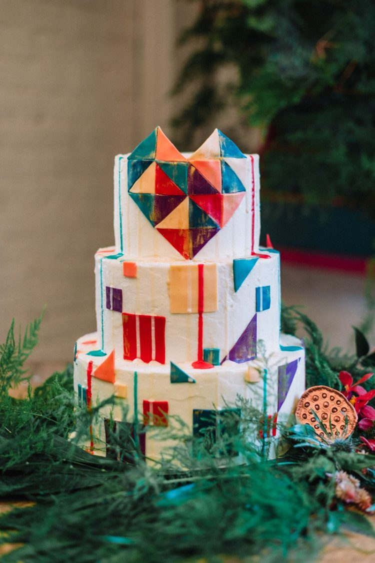 The wedding cake is a bold and geometric, the display is decorated with boho vibes, fern and flowers
