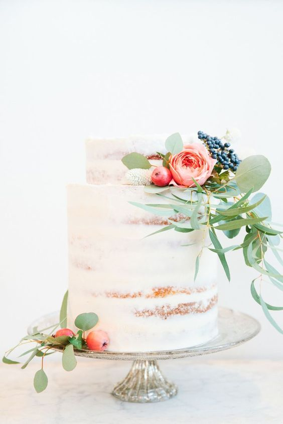 semi naked two-tiered wedding cake with flowers and berries