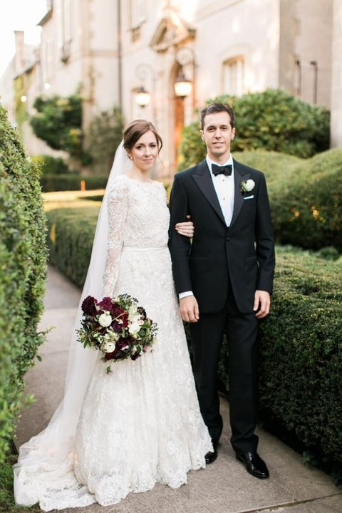 the groom is a classic black tux, the bride is a long sleeve lace wedding dress